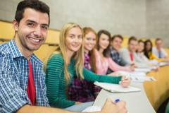 Smiling students in a row at the lecture hall Stock Photos