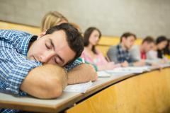 Male sleeping with students in lecture hall Stock Photos
