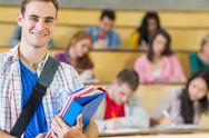 Stock Photo of Smiling male with students sitting at lecture hall