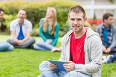 Smiling college boy holding tablet PC with students in park Stock Photos
