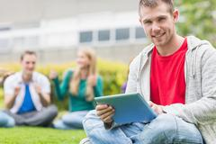 Smiling college boy holding tablet PC with students in park - stock photo