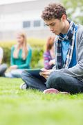 Stock Photo of College boy using table PC with blurred students in park