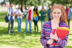 Stock Photo of College girl holding books with students in park