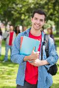 Stock Photo of College boy holding books with blurred students in park