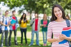 College girl holding books with blurred students in park Stock Photos