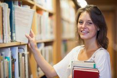 Stock Photo of Smiling female student selecting book in the library