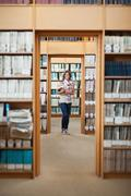 Full lenght of a female student standing in the library Stock Photos
