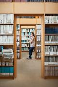 Full length of a female student standing in the library Stock Photos