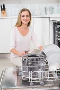 Cheerful gorgeous model kneeling behind dish washer - stock photo