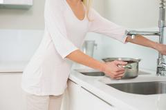 Woman filling pot with water - stock photo