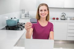 Gleeful casual woman using laptop and credit card - stock photo