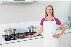 Casual happy blonde standing next to stove top Stock Photos