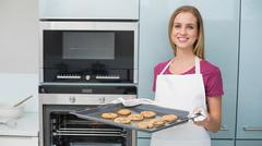 Casual content woman holding baking tray with cookies - stock photo