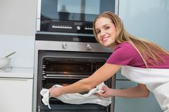 Casual happy woman taking baking tray out of oven - stock photo