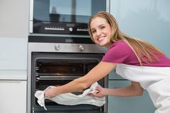 Casual smiling woman putting baking tray in oven - stock photo