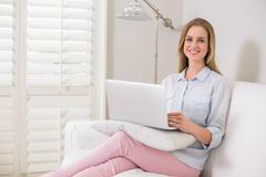 Gleeful casual blonde sitting on couch using laptop - stock photo