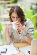 Student drinking coffee while using laptop at cafeteria table Stock Photos