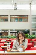 Gloomy student in the cafeteria with food tray - stock photo