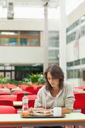Stock Photo of Sad student in the cafeteria with food tray