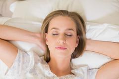 Natural calm woman napping in bed - stock photo
