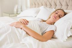 Natural calm woman slumbering in bed - stock photo