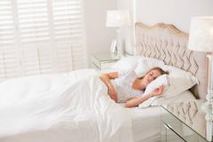 Natural calm woman resting in bed - stock photo