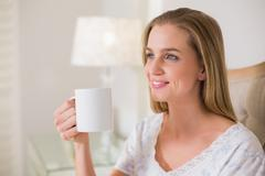 Natural happy woman sitting on bed holding mug Stock Photos