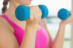Mid section of a woman exercising with dumbbells in fitness studio - stock photo