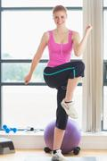 Beautiful young woman performing aerobics exercise - stock photo