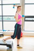 Stock Photo of Woman performing step aerobics exercise with dumbbells