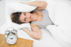 Annoyed young woman lying on her bed covering her ears with pillows Stock Photos