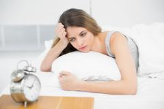Stock Photo of Calm attractive woman lying thoughtful on her bed