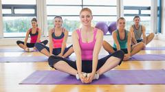 Fitness class and instructor doing the butterfly stretch - stock photo