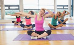 Fitness class and instructor stretching hands on yoga mats - stock photo