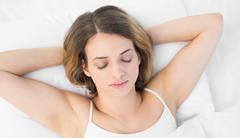 Overhead view of pretty calm woman sleeping lying on her bed - stock photo