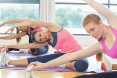 Stock Photo of Class and instructor doing stretching pilate exercises