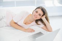 Gleeful young woman posing lying on her bed smiling at camera - stock photo
