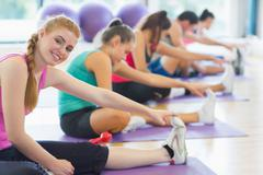 Instructor with class stretching legs in exercise room Stock Photos