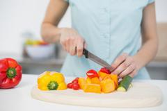 Mid section of young slender woman cutting vegetables Stock Photos