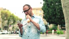 Man eating baguette and texting on cellphone in the city HD Stock Footage