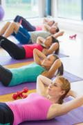 Stock Photo of Sporty fitness class doing sit ups on exercise mats