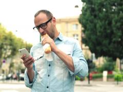Man eating baguette and texting on cellphone in the city NTSC Stock Footage