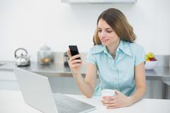 Content brunette woman making use of her smartphone holding a cup - stock photo