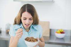 Happy brunette woman eating cereals standing in her kitchen - stock photo