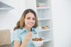 Cute woman holding a bowl with cereals while smiling at camera - stock photo