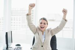 Happy cheering woman raising her arms sitting on her swivel chair - stock photo