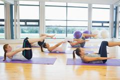 Class stretching on mats at yoga class in fitness studio Stock Photos