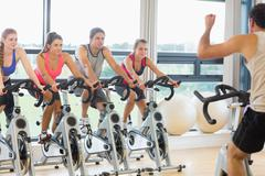 Man teaching spinning class to four people - stock photo