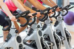 Mid section of people working out at spinning class - stock photo