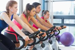 Stock Photo of Four people working out at spinning class